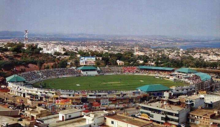 Quaid-e-Azam Cricet Stadium in Mirpur, Azad Kashmir with picturesque Mangla Lake in the background.